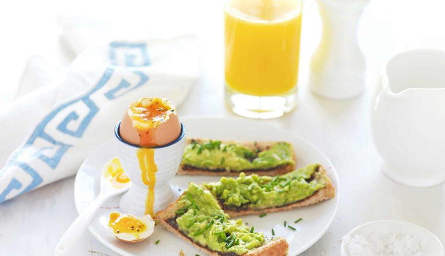 Café da manhã com ovos cozidos, abacate e suco de laranja